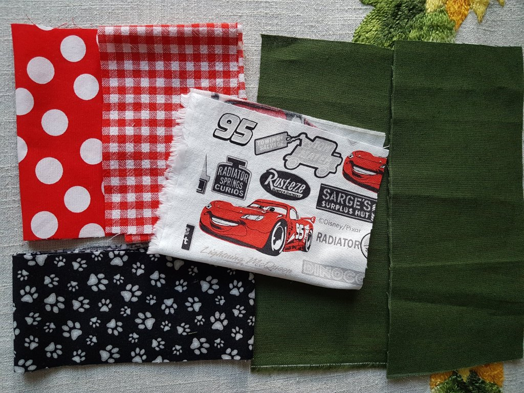 Fabrics for Face Masks: There are these different fabrics: Red bottom with white dots, white and red checked, black bottom with white cat feet, white bottom with red cars and text on white and black bottom, a whole, quite dark green one.