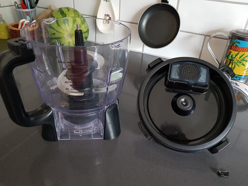 Food processor with the lid on the side of it and in front of the lid lies the little security button