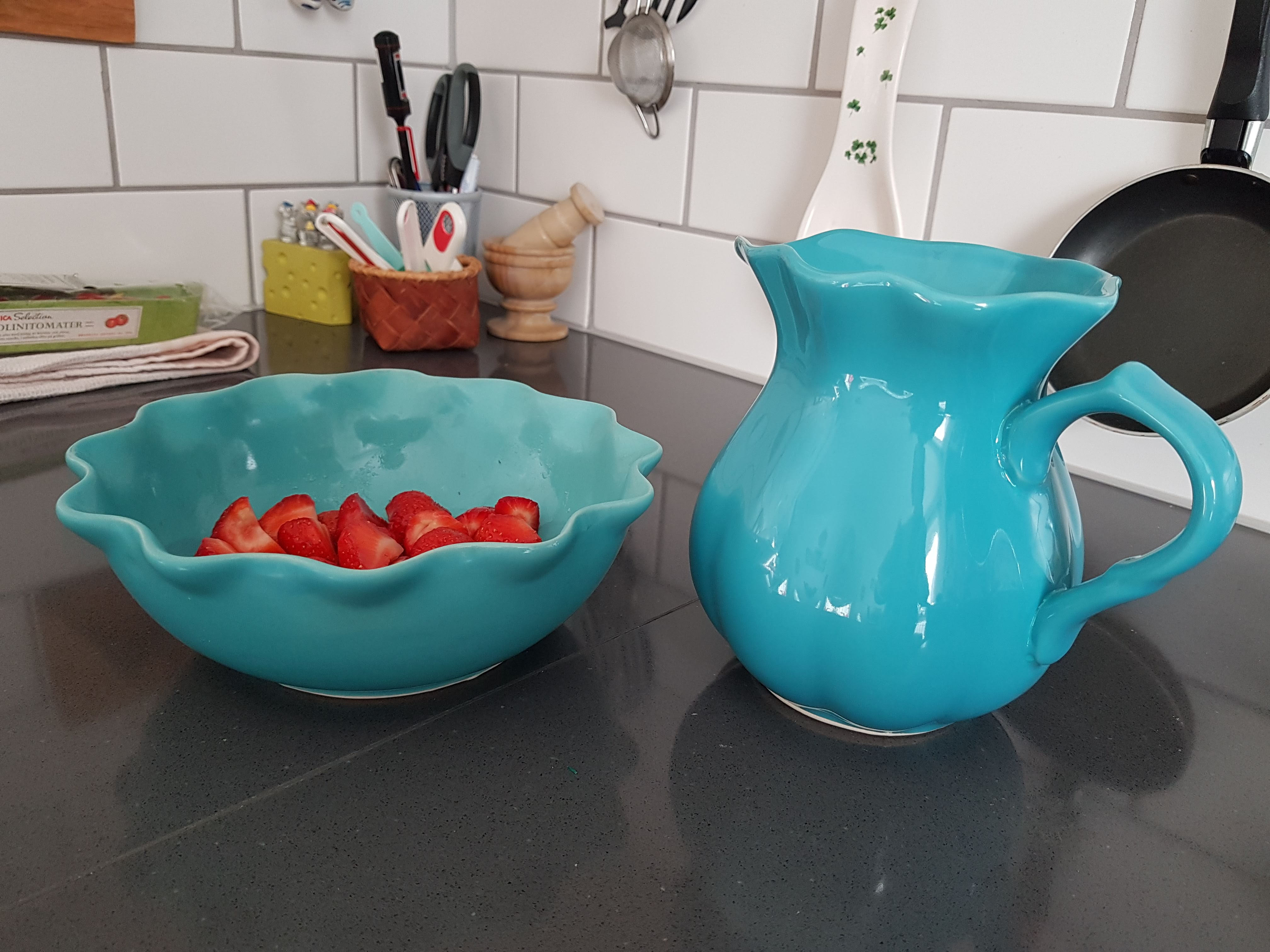 A turquoise bowl (with some strawberries) and jug